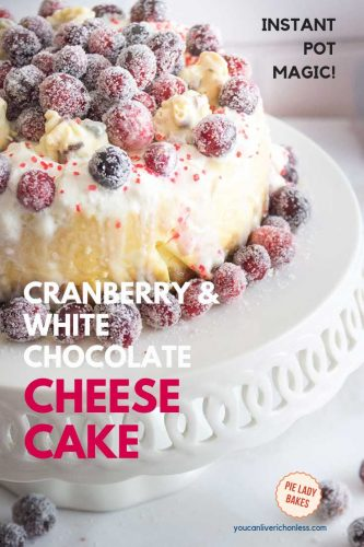 cranberry & white chocolate cheesecake text overlay on image of cheesecake with sugared cranberries on white cake plate with white brick  background, black text in upper right corner says instant pot magic