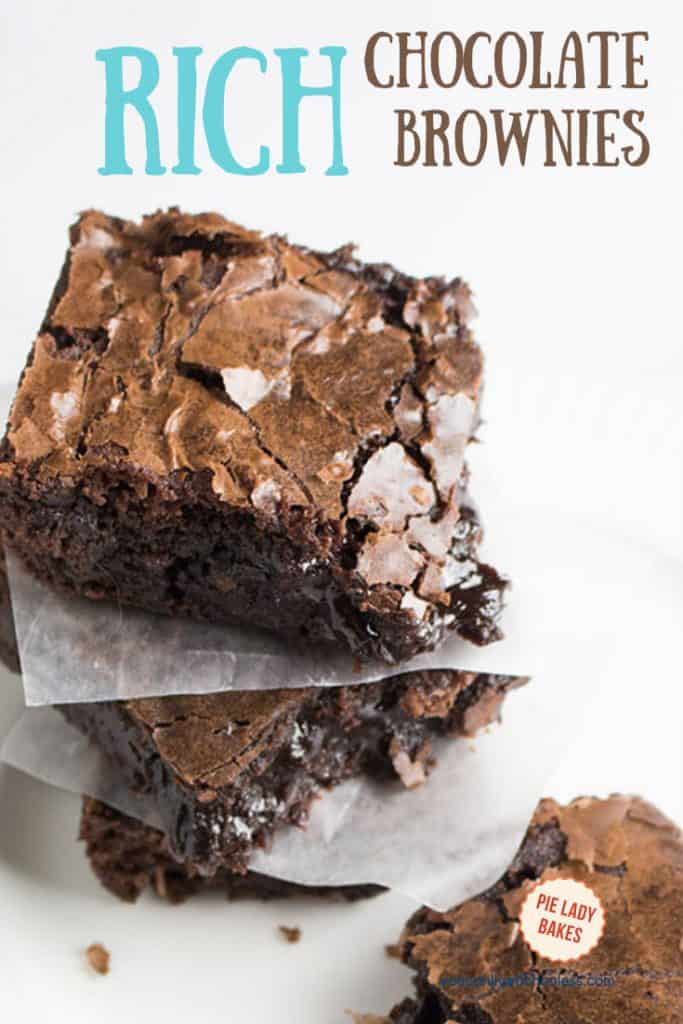 two brownies stacked on waxed paper with one gooey chocolate brownie to the right all on a white plate and text for pinning