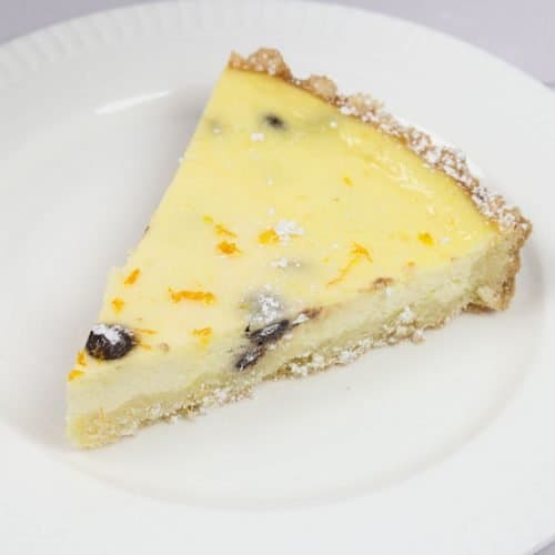 slice of ricotta pie or sweet Italian easter pie on white plate with powdered sugar