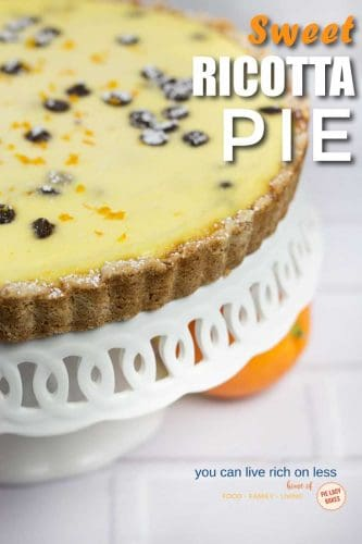 side view of ricotta pie on white scalloped cake plate with orange peeking out at the side and text sweet ricotta pie on top