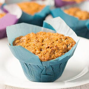 tomato soup spice cake muffin in blue muffin wrapper on white plate with other muffins in background