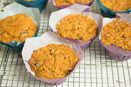 several muffins in blue and purple baking cups on a baking rack