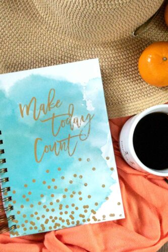 straw sunhat at top clockwise a mandarin orange, cup of coffee in a white mug blue watercolor cover on a journal with gold speckles and script lettering that says make today count
