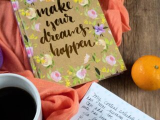coffee, orange shawl, gold lettering on a floral patterned journal that says make your dreams happen a mandarin orange and the corner of a journal page with writing on it