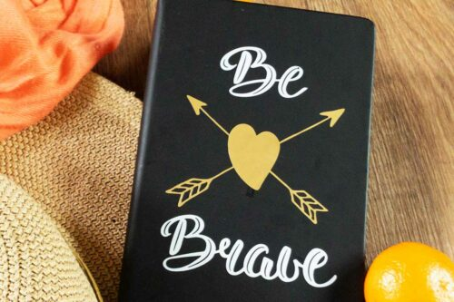 black covered journal with white and gold lettering that says be brave with a gold heart in the centre and arrows criss crossed coral shawl, sunhat and mandarin orange in the background