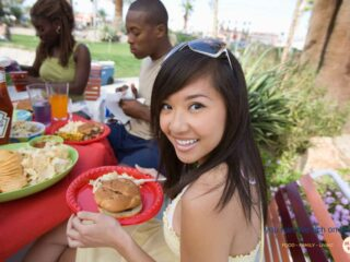 girl with long black hair and sunglasses on her head with a red picnic plate and hamburger and salad on it, with friends eating outside in the backgroun