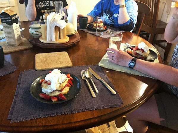 round wooden dining table with friends sitting getting ready to eat strawberry shortcake
