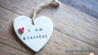 heart pendant with jute tied to it on a wooden table says i am grateful in small lower case type and a small pink heart attached
