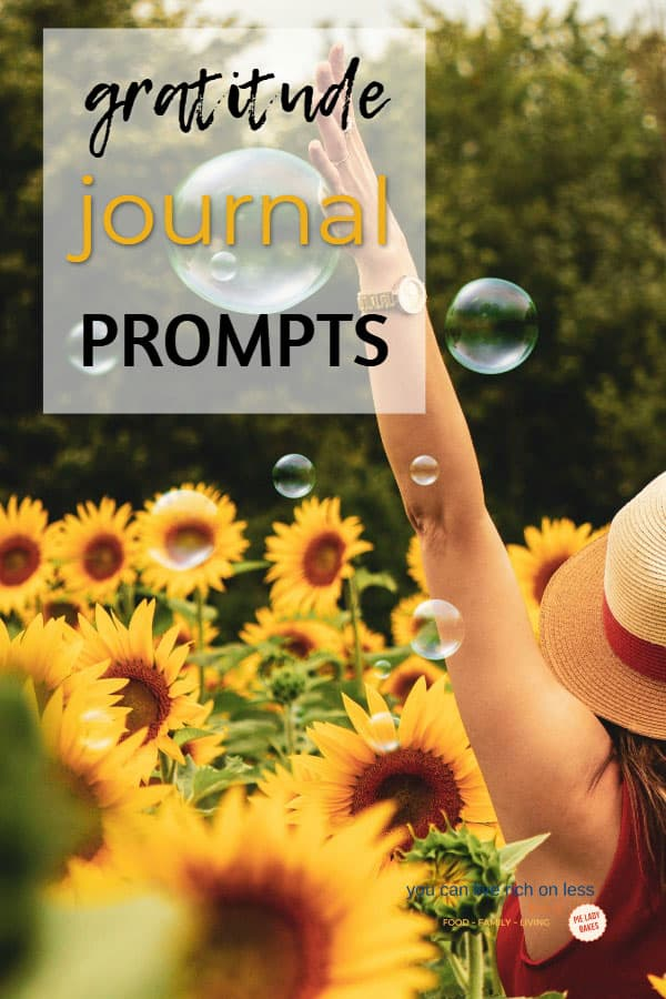 woman wearing a straw hat with arms outstretched standing in a field of sunflowers. text says gratitude in yellow type, with bubbles floating around here, and her back is to the camera