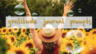 field of sunflowers, woman in white straw hat and dark orange dress with arms flung upwards to the sky text reads gratitude journal prompts on white box background