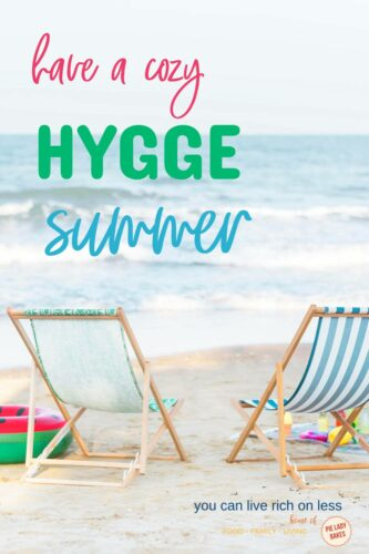 two beach chairs on the sand with ocean in front beach toys in background text says have a cozy hygge summer