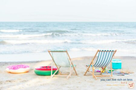 two empty beach chairs, one blue & white stripes, colourful toys in the background