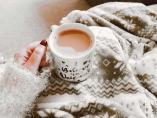 arm in cozy sweater holding a cup of coffee person is wrapped in cozy blankets
