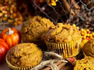 pumpkin muffs with fall decorations cinnamon sticks, wire container in background full of pine cones