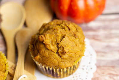 one pumpkin muffin on a white paper doily with an orange gourd in the background