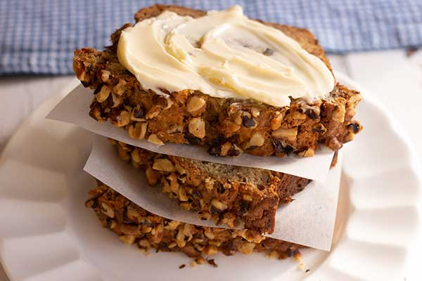 slices of banana nut bread stacked one on top of the other, top slice is slathered in butter on a white plate with blue checked placemat in background