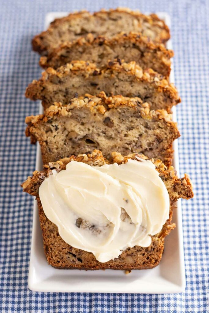 four slices of starbucks banana bread on a white plate set on a blue checked placemat one slice is covered in butter