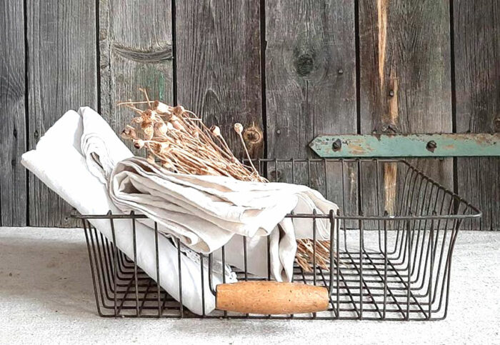 antique storage wire basket, with napkins and dried flowers inside and barnboard background