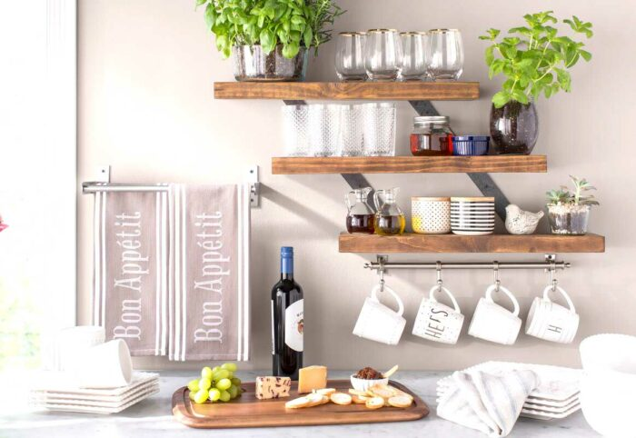 kitchen pantry wall shelves with mugs, jars, glasses and plants on them above a counter with a bottle of wine, cutting board, and tea towels on a rack