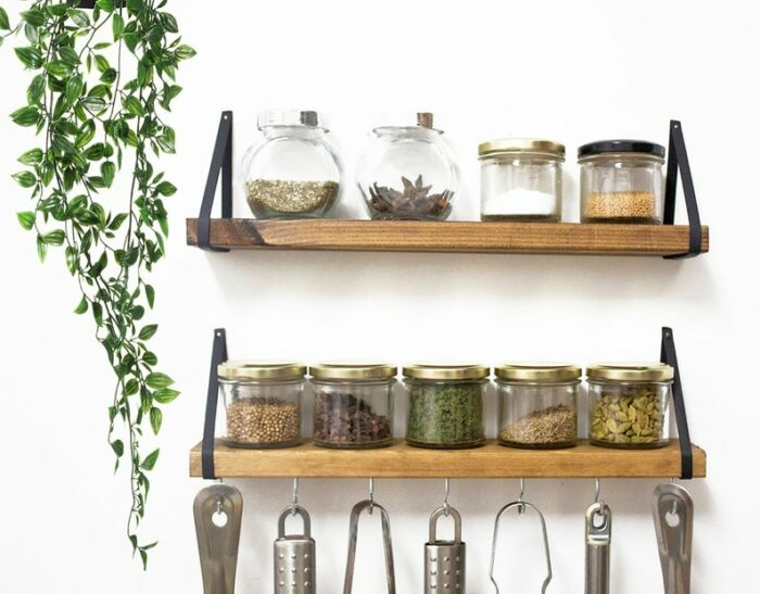 wooden shelves with metal side straps and hooks for utensils has spice jars on two shelves