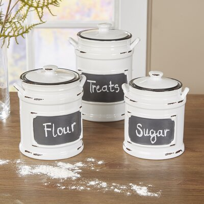 grey and white ceramic cannister set for Flour, Treats, Sugar on a dark wooden counter, with flour spilled