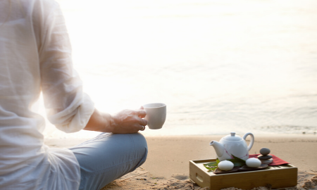 woman with tea up in hand sitting crosslegged on a beach with tea set beside her.