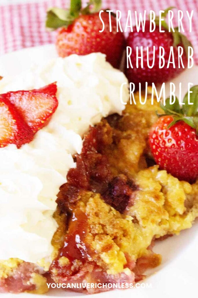 strawberry rhubarb crumble with whipped cream and sliced strawberries background shows white plate and red checked placemat