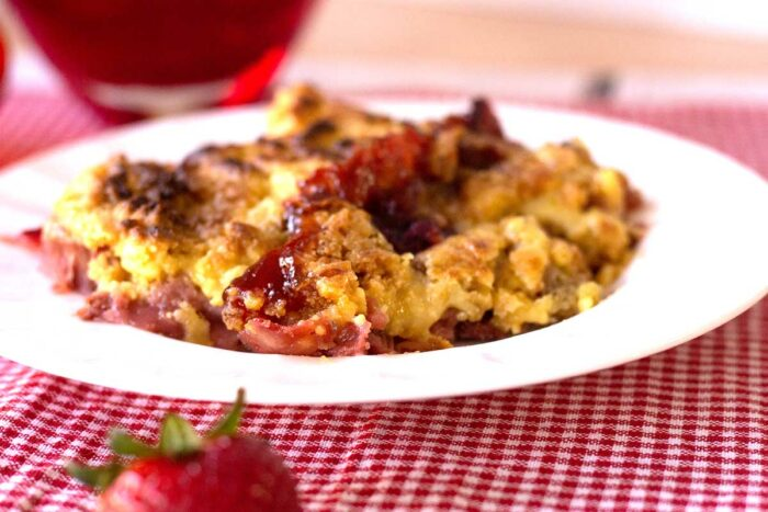 serving of strawberry rhubarb crumble on a white plate on red checked tablecloth