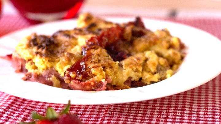 strawberry rhubarb crumble on a white plate with red checked placemat