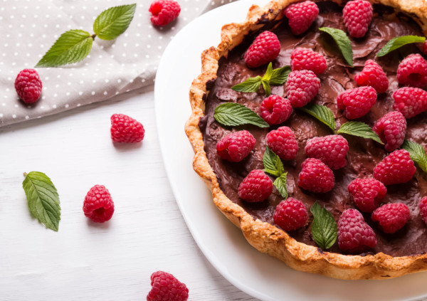 chocolate tart with fresh raspberries and mint on a white plate