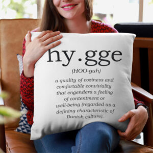 woman holding a pillow that has the definition of hygge printed on it