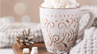mug of cocoa with marshmallows and soft blanket for a hygge holiday