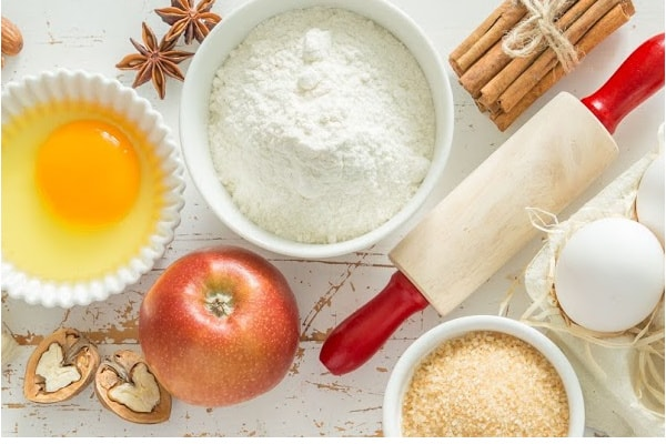 table top with ingredients to bake with apples, cinnamon sticks, egg in white bowl, sugar, small rolling pin