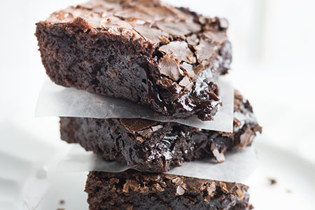 3 gooey chocolate brownies stacked with parchment paper in between