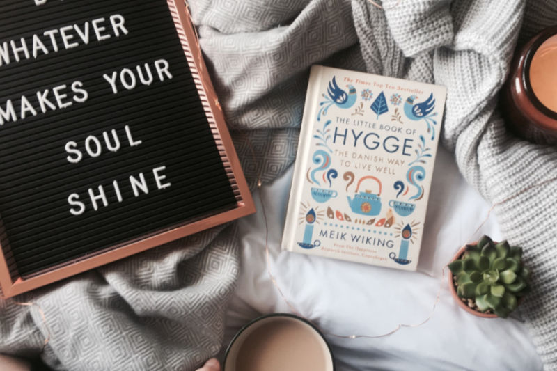 letter board that reads whatever makes your soul shine beside The Little Book of Hygge on a blanket with a candle and succulent plant to the side and bottom right