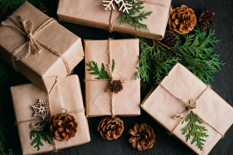 best hygge books with brown paper wrapping on books as gifts with pine cones and greenery, tied with twine
