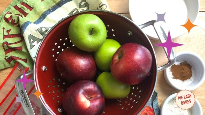 green and red apples in red colander on a printed tea towel with ingredients ready to make apple pie filling