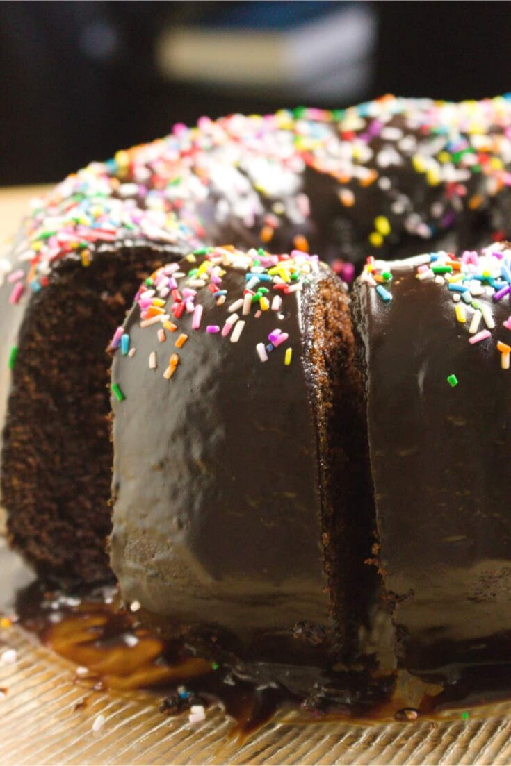 close up image of chocolate buttermilk bundt cake sliced with funfetti sprinkles on top of chocolate frosting