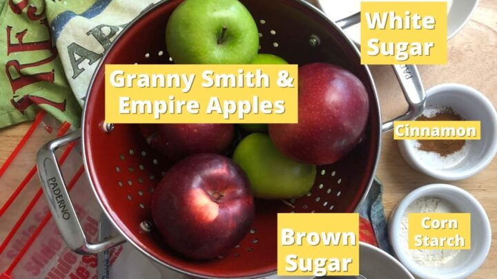 display of ingredients for freezer apple pie filling includes apples in a red colander on a printed tea towel, white sugar, brown sugar, cinnamon, corn starch & freezer bags