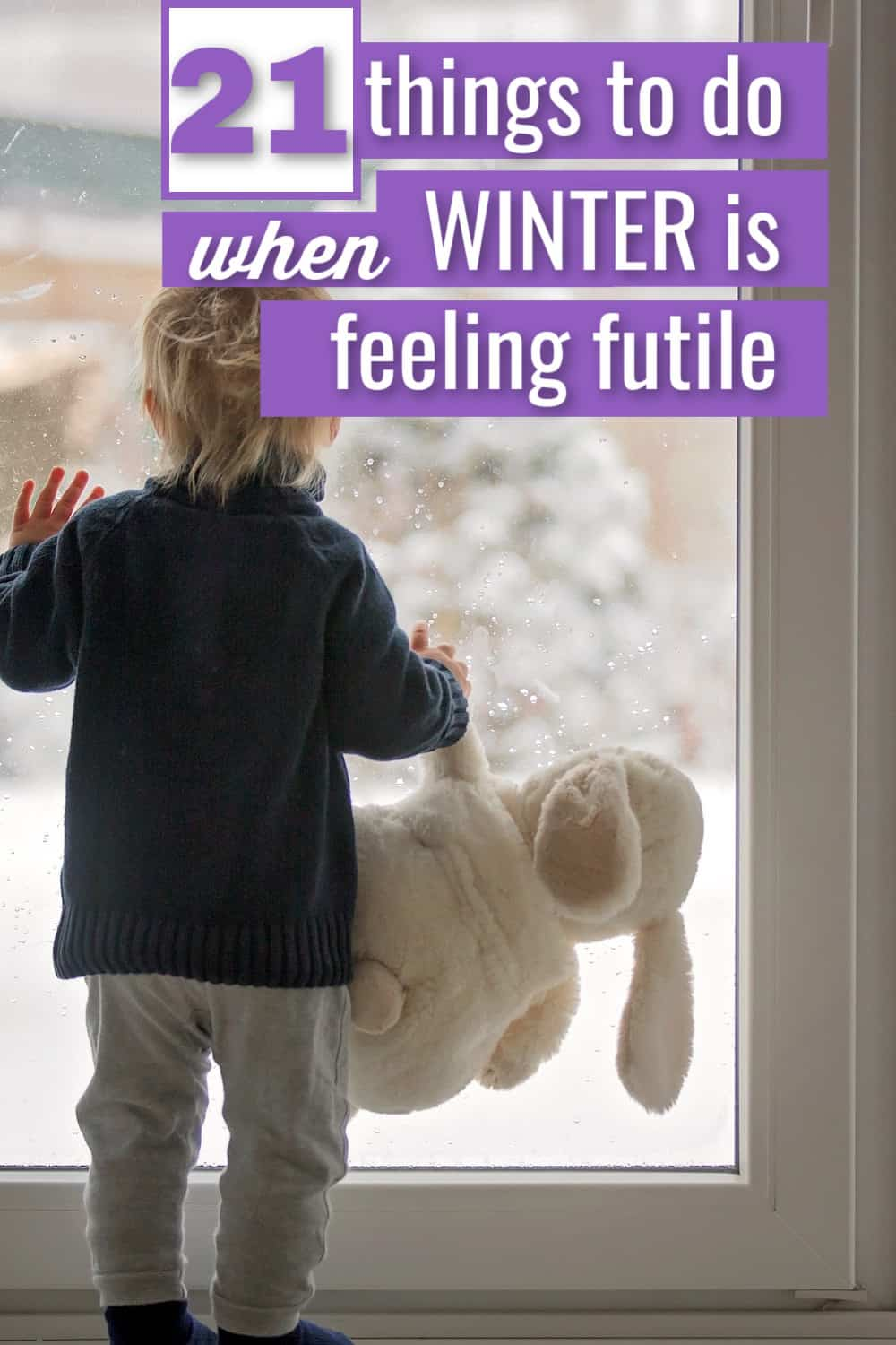 small child  with bunny rabbit looking out a glass door at winter
