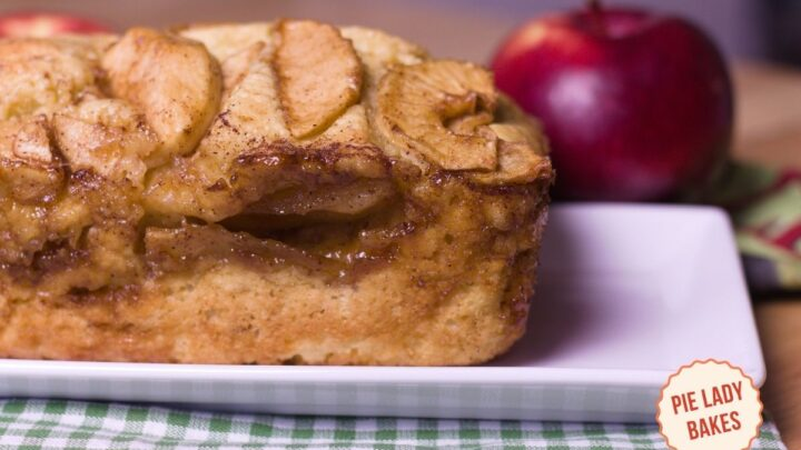 apple pie bread side view shows cinnamon, butter, apples, brown sugar on a white plate green & white checked cloth and red apple in background