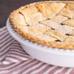 freshly baked cherry pie with a braided and lattice top butter pie crust on a white and red table runner