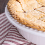 side view of baked pie with braided pie crust edging on a lattice pie crust. pie is in a white dish with red and white striped table napkin