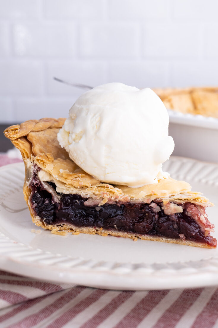 slice of grandma's cherry pie on a white plate with a scoop of vanilla ice cream on top white brick wall in background
