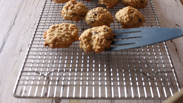 blue spatula placing ranger cookie on cooling rack