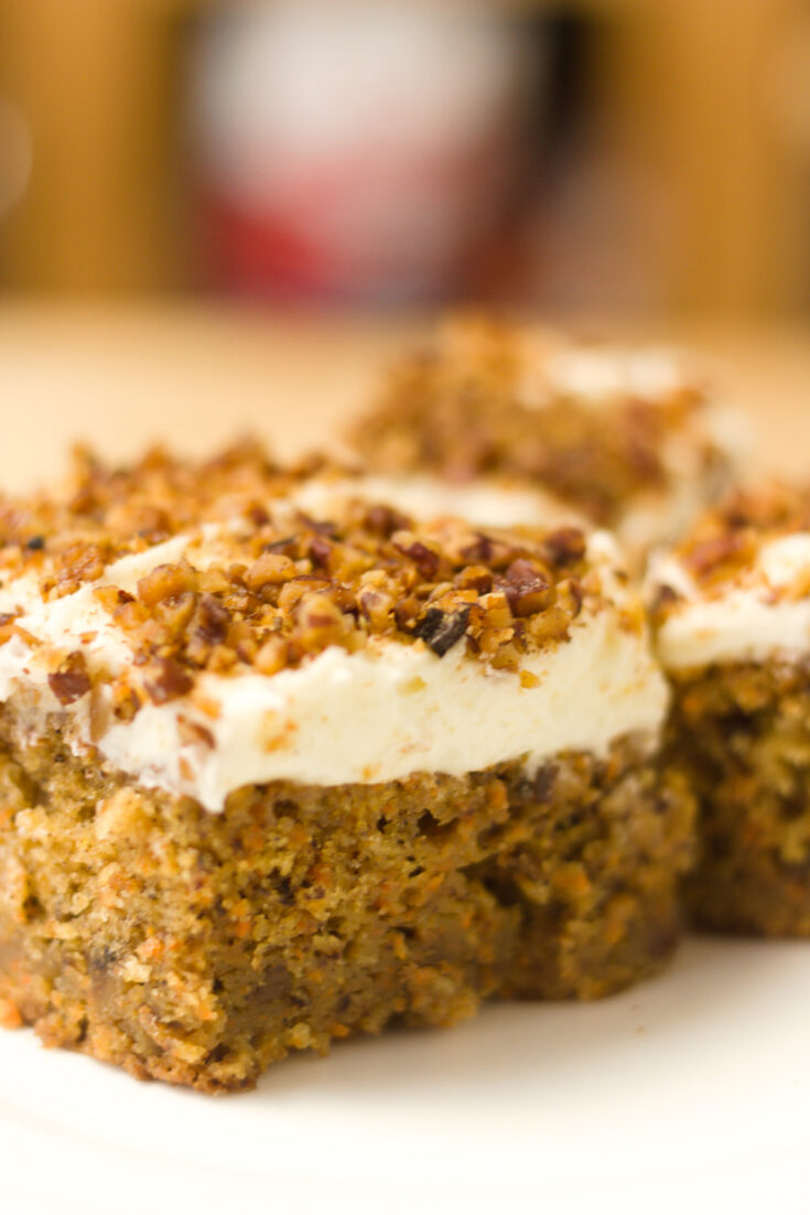 closeup view slice of carrot cake with cream cheese frosting sprinkled with toasted pecans on top of frosting