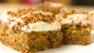slices of carrot cake with cream cheese frosting on a white plate