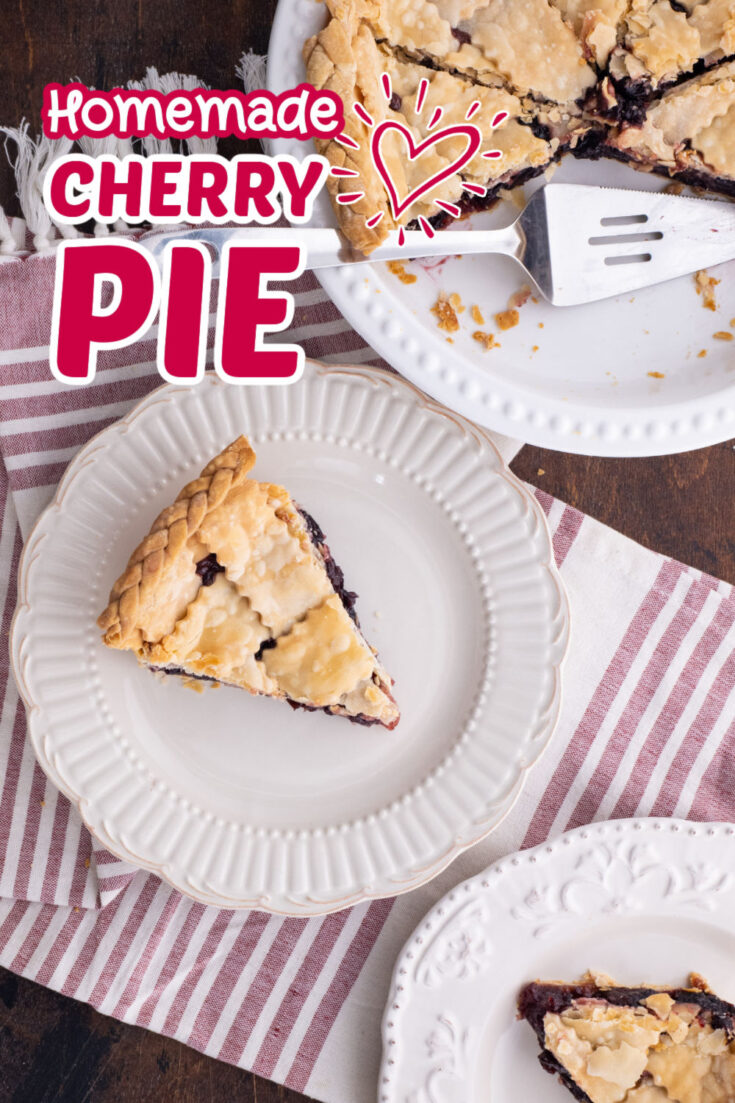 overhead view of two pieces of cherry pie on white plates with rest of pie in a white pie dish with pie server on a pink & white striped table runner