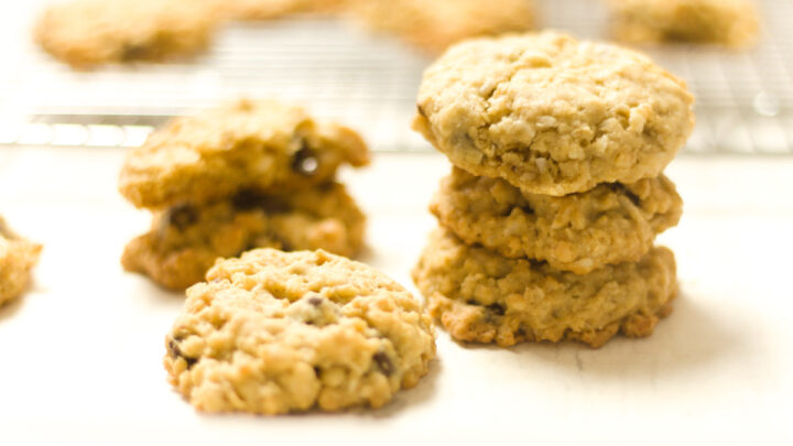 stack and single ranger cookies on a white counter with blurred out cookies on a cooling rack in background