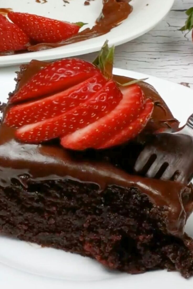 piece of chocolate cake with sliced strawberries on top shows fork ready to take a bite of cake white plate with rest of cake in background